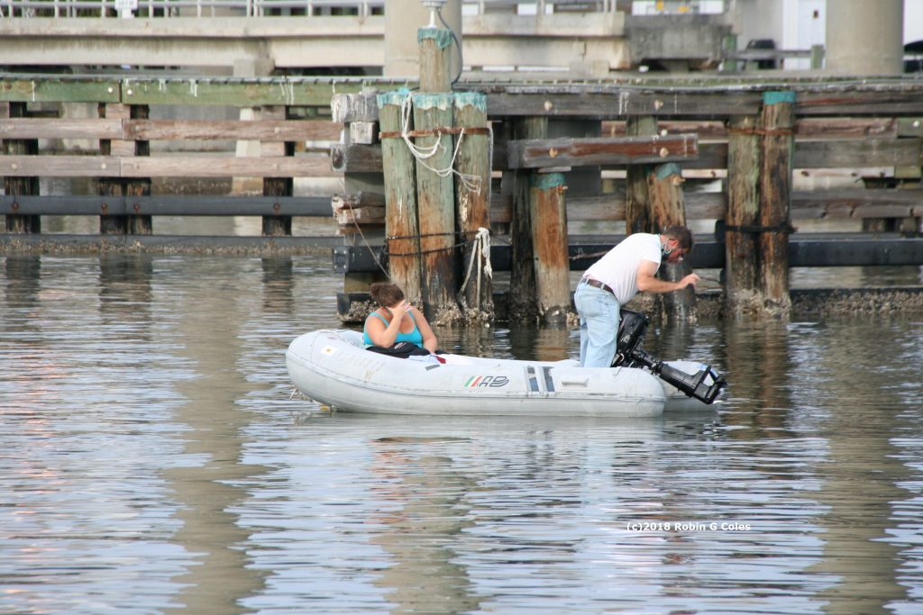 couple in their inflatable dinghy. He's trying to untangle fishing line.